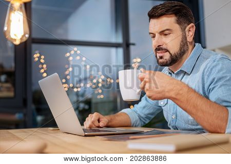 Small break. Pleasant hard working smart man holding a cup with tea and enjoying his drink while taking a small break