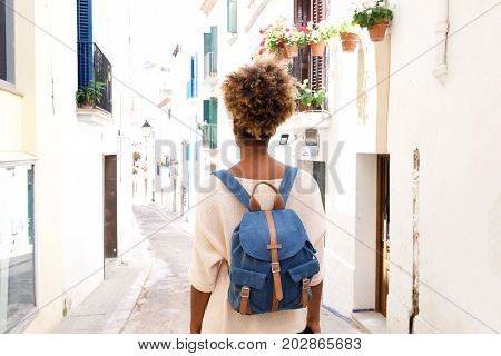 Rear View Portrait Of African American Woman Walking On Street With Bag