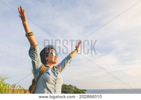 Happy young traveler woman raised arm up to sky enjoying a beautiful of nature at top of mountain and sea viewFreedom wanderlust backpacker conceptvintage filter