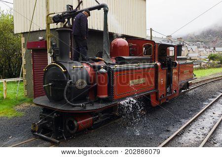 Blaenau Ffestiniog Wales UK - September 4 2017: Narrow gauge steam locomotive David Lloyd George of the Ffestiniog Railway Company having her water tanks filled