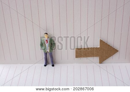 Figurine And An Paper Arrow In A Notebook