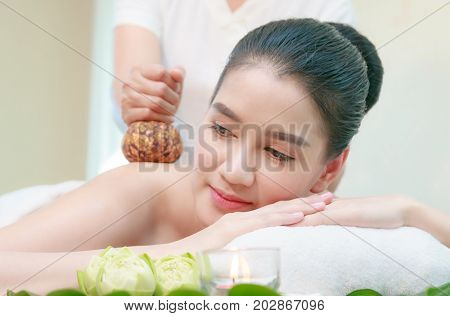 Young Asian Woman Having Thai Herbal Compress Massage In Spa Environment.
