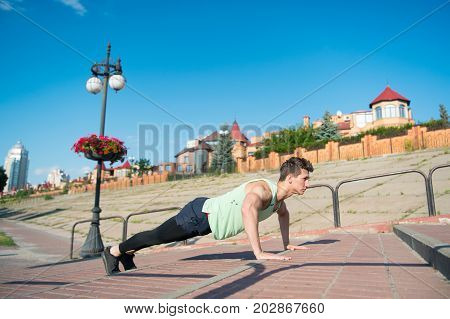 Macho Doing Pushups On Red Brick Stairs Outdoors
