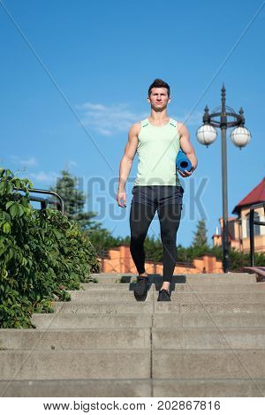 Man athlete in tracksuit with gym yoga mat going downstairs on sunny summer day on blue sky outdoors. Workout and training. Sport and fitness. Healthy lifestyle concept.