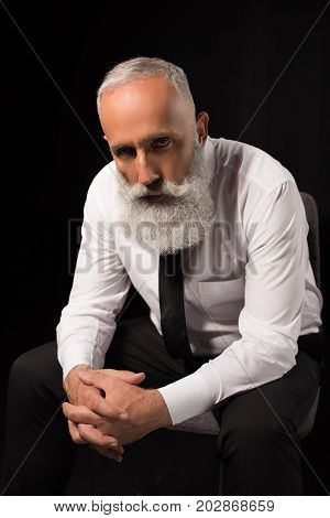 Man Sitting With Hands Clasped
