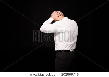 Man Clasping Hands On Nape Of Neck