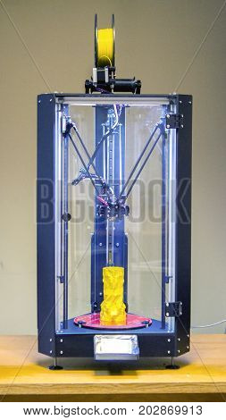 Three-axis 3D printer. inside stands a model of a vase of yellow color