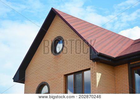 Brick house with attic window and red asphalt shingles roof. Roofing Construction.