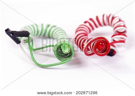 Red and green diodes on helical conductors are isolated on white