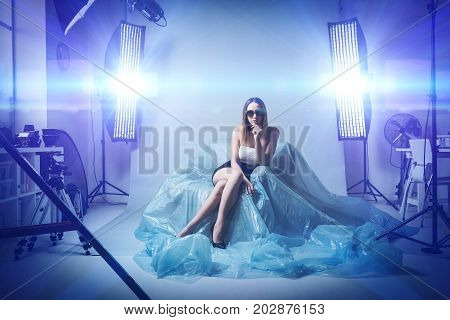 Beautiful fashion model doing a professional photo shoot she is wearing sunglasses and an elegant dress softboxes and flashes on the background
