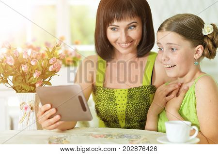 Smiling mother and daughter sitting at table and using digital tablet