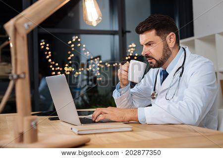 At the hospital. Serious hard working male doctor working on a laptop and having coffee while having a night shift at the hospital
