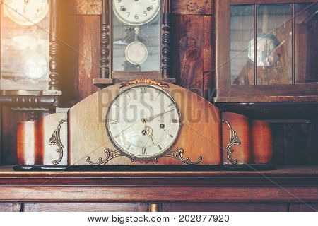 Collectible varieties of antique clocks hanging on the wall or placing on wooden cabinet