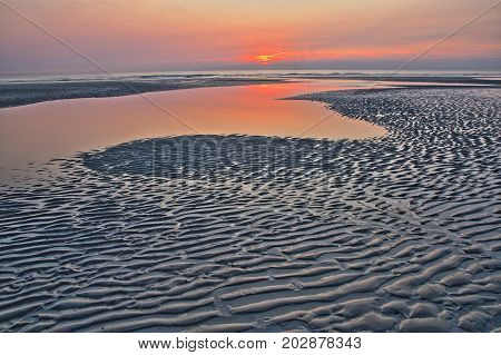 The beach of Ambleteuse at sunset with patterns on the sand in the foreground, Cote d'Opale, Pas de Calais, Hauts de France