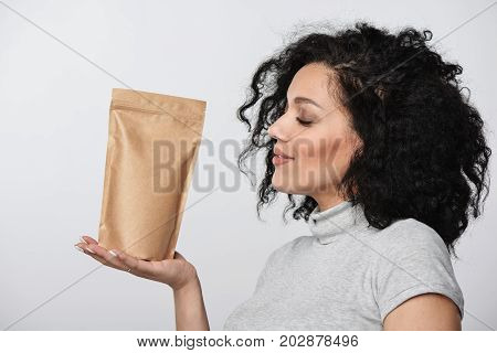 Profile closeup portrait of a woman holding craft paper pouch bag with copy space over grey background.