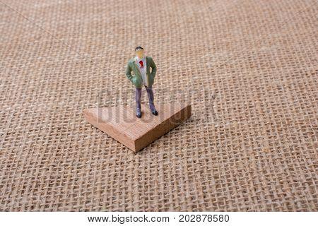 Man Figurine Standing On A Triangle