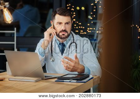 I am listening. Serious professional male physician putting a phone to his ear and listening to his interlocutor while receiving a call