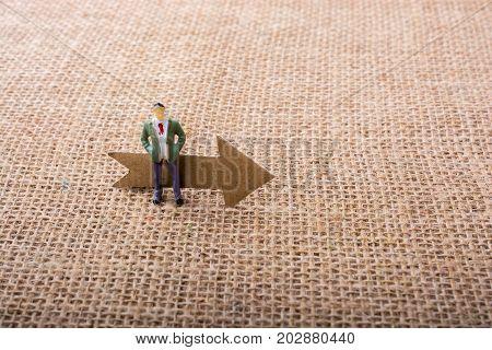 Figurine Man Led By An Arrow On Canvas