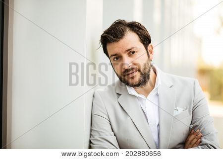Elegant Man In Grey Suit In A Business Center