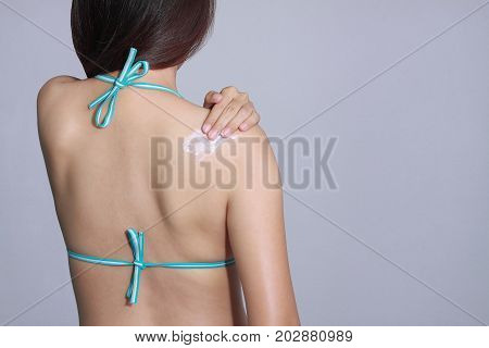 woman wear bikini applying sunscreen on her back. SPF and UV sunblock protection concept. Travel vacation
