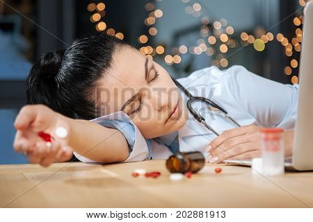 Too exhausted. Tired hard working female scientist holding pills in her hand and sleeping while being too exhausted