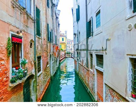 Classical picture of the venetian canals with boats across the canal.
