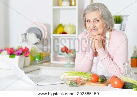 Smiling senior woman holding hands on chin while leaning on table with laptop and vegetables