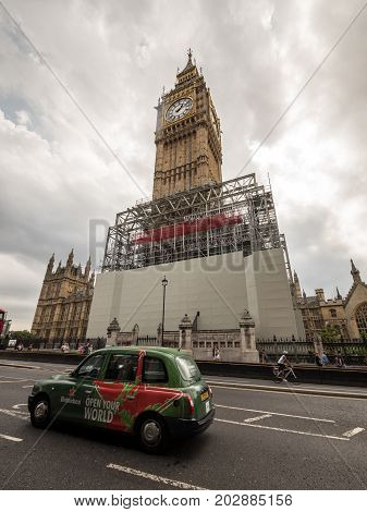 LONDON UK - 29 AUGUST 2017: A London taxi passing by the iconic Big Ben landmark clock tower in Westminster. The tower has been silenced and is being prepared for renovation work with heavy scaffolding.