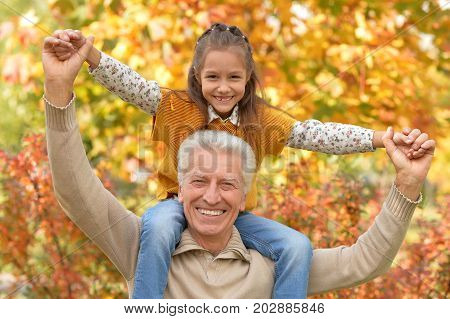 Grandfather and granddaughter having fun in autumnal park