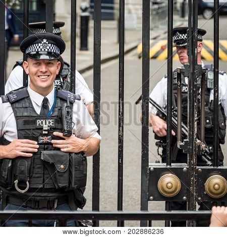 LONDON UK - 29 AUGUST 2017: A friendly smile on the face of a London policeman standing outside the gates of Downing Street with armed colleagues in the background.