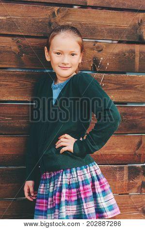 Outdoor portrait of pretty little 7-8 year old schoolgirl wearing school uniform