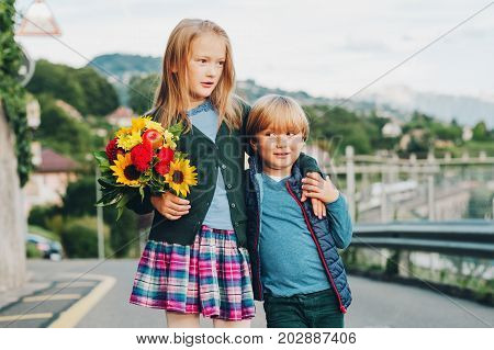Outdoor portrait of a cute little kids with beautiful bouquet of autumn flowers. School fashion for children schoolwear