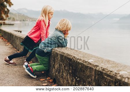 Two funny kids enjoying nice and warm autumn day next to lake Geneva. Little brother and big sister spending time together outside
