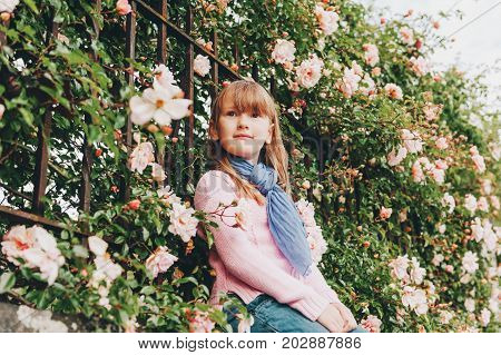 Outdoor portrait of pretty little 7 year old girl wearing pink pullover and blue scarf posing between soft light roses. Autumn fashion for children