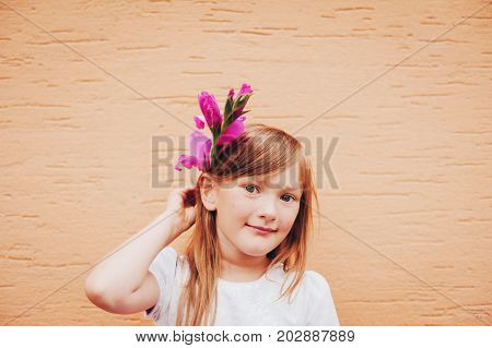 Candid portrait of adorable little 6-7 year old girl holding pink flower next to head