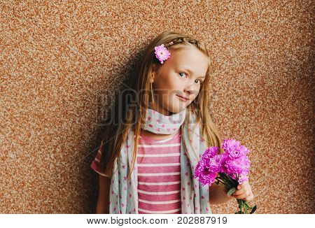 Candid portrait of adorable little 6-7 year old girl holding pink chrysanthemum flowers
