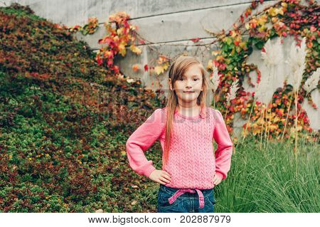 Outdoor portrait of pretty little 7 year old girl wearing pink pullover. Autumn fashion for children