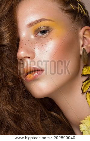 Portrait of beautiful red-haired girl with brightly colored art makeup and curls. Beauty face. Photo taken in the studio.