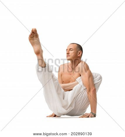 Mature shirtless muscular man wearing wide trousers practising yoga isolated on white