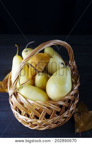 fresh pears in a wicker basket with autumn leaves on a dark wooden background copy space flat lay
