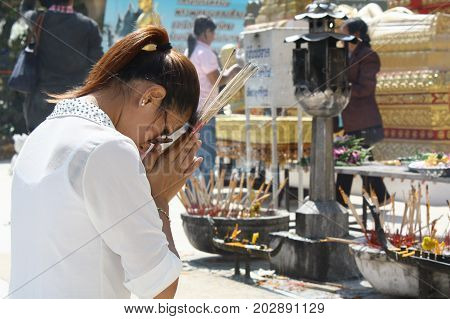 NAKHONPRANOM, THAILAND -February 23 :At  PhraThatPhanom Buddhist temple Asian woman pay homage to a Buddha image , February 23, 2013 in NakhonPranom Province , Thailand.