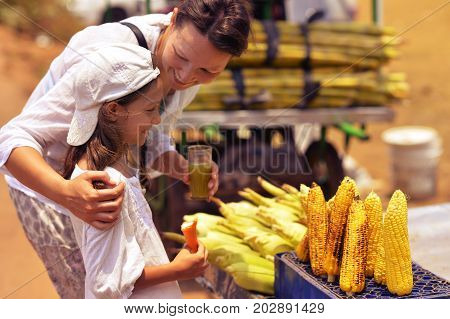 Mother and daughter buying food on street