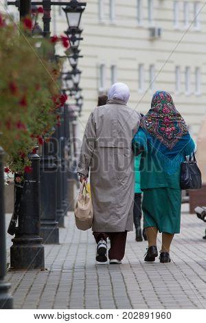 Two elderly women in tatar traditional shawl - rear view, vertical shot