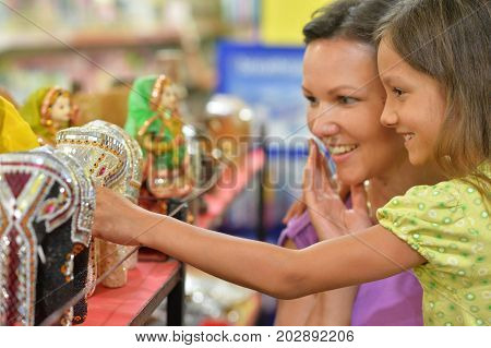 Mother and daughter choosing souvenirs in store