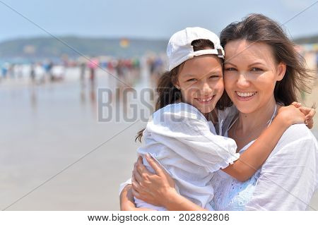 Mother hugging her cute little daughter on seashore