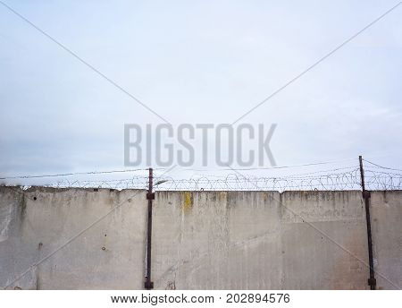 Concrete wall against the backdrop of barbed wire the concept of prison salvation Refugee lonely space for text