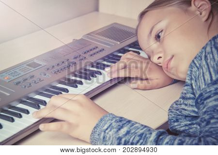 Girl is tired of learning to play the synthesizer and sad lies on the table
