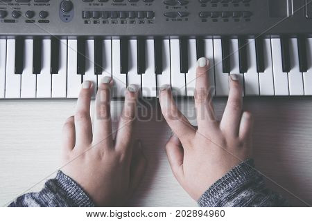 Beautiful girls hands playing electronic piano keyboards