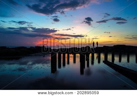 Long exposure of colorful sunset sky,reflection,concrete pile in the lake and silhouette of couple enjoying romantic sunset.