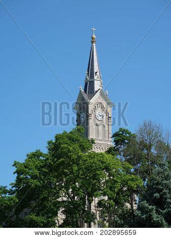 The sunlit steeple of St. Mary's Catholic Church built on a high bluff in 1882 towers above treetops and buildings in small town Port Washington Wisconsin.